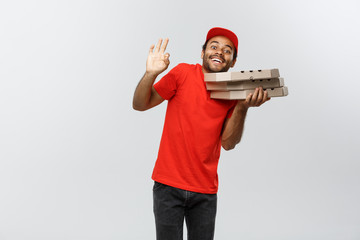 Delivery Concept - Portrait of Handsome African American Pizza delivery man making ok sign with fingers. Isolated on Grey studio Background. Copy Space.