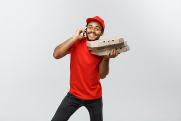 Delivery Concept - Portrait of Handsome African American Pizza delivery man on phone with customer. Isolated on Grey studio Background. Copy Space.