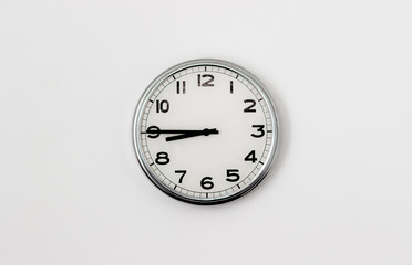 White Clock hanging on a white wall showing time 8:45