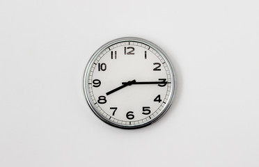 White Clock hanging on a white wall showing time 8:15