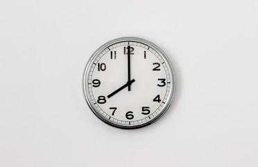 White Clock hanging on a white wall showing time 8:00