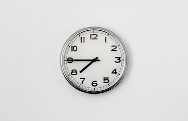 White Clock hanging on a white wall showing time 7:45