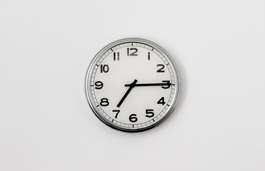 White Clock hanging on a white wall showing time 7:15