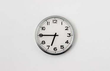 White Clock hanging on a white wall showing time 6:45