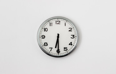 White Clock hanging on a white wall showing time 6:30