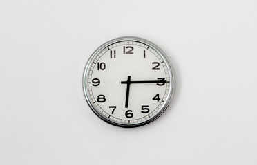 White Clock hanging on a white wall showing time 6:15
