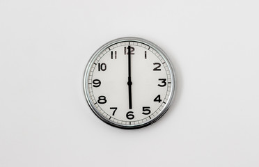 White Clock hanging on a white wall showing time 6:00