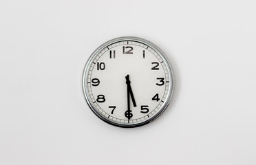 White Clock hanging on a white wall showing time 5:30