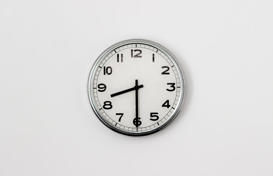 White Clock hanging on a white wall showing time 8:30