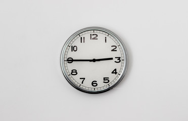White Clock hanging on a white wall showing time 2:45