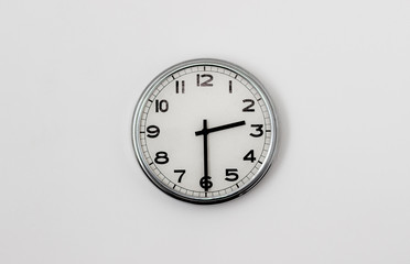 White Clock hanging on a white wall showing time 2:30