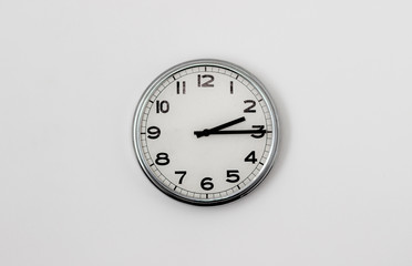 White Clock hanging on a white wall showing time 2:15