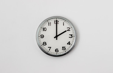 White Clock hanging on a white wall showing time 2:00