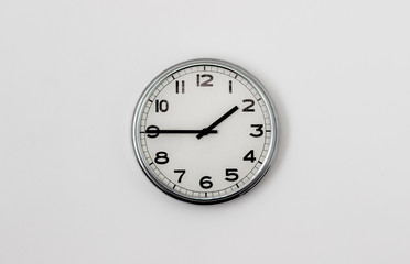 White Clock hanging on a white wall showing time 1:45
