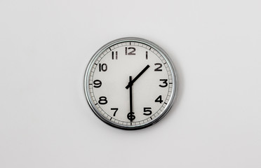 White Clock hanging on a white wall showing time 1:30