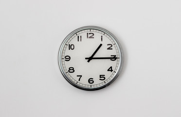 White Clock hanging on a white wall showing time 1:15