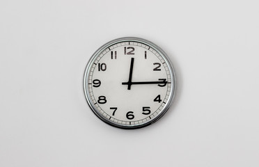 White Clock hanging on a white wall showing time 12:15