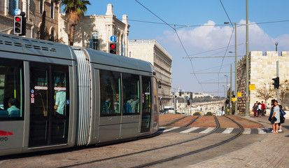 Modern tram goes along the street of Jerusalem.