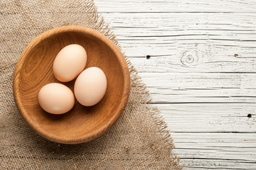 chicken eggs in wooden plate on white wooden background
