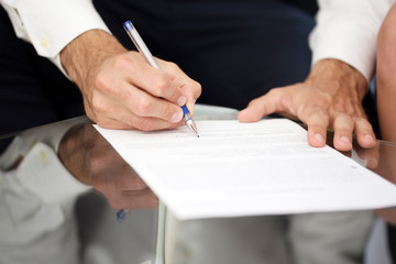 Young businessman signing contract on desk