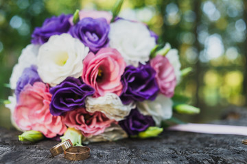 wedding rings and bouquet on the wooden surface