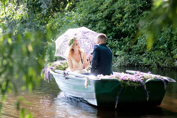 Romantic love story in boat. Woman with wreath and white dress under lace umbrella