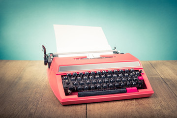 Retro old typewriter from 70s with paper blank on wooden table. Vintage style filtered photo