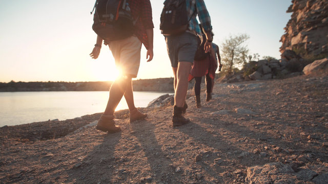 Anonymous group of multiethnic people with backpacks walking on rocky shore in sunlight while hiking.
