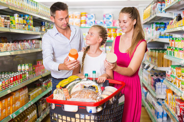 Parents with girl choosing  goods and standing near shopping cart