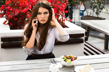 Stunning brunette with long hair sits before red flowers