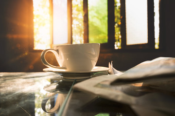 Coffee cup with news paper at coffee shop, summer vintage with sunlight background.
