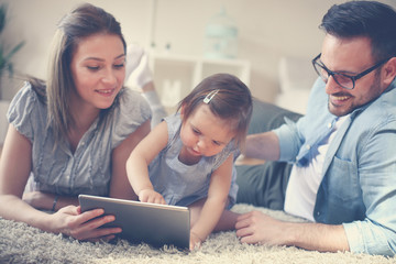 Family lying on the floor with their baby. Family using digital tablet together on the floor.