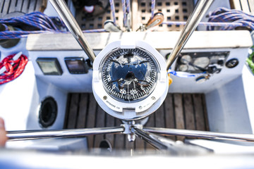 A compass, a view from above the steering wheel on a yacht.