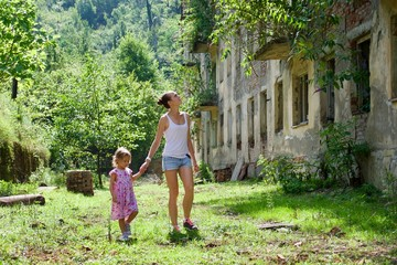 Young mother with little daughter walking in dead city with ruins