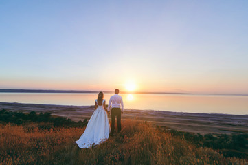 Bride and groom are walking together at sunset near the sea