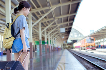 Young girl asian backpack traveler waiting with carrying hold suitcase luggage booking ticket in train station railway platform vacation time in holiday relaxation.