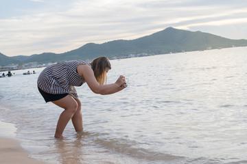 girl take photo on the beach