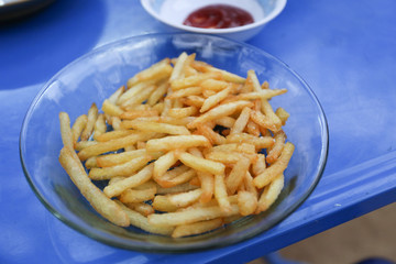 French fries on transparent dish on blue table