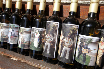 Oskar Meglic's, a retired butcher, impersonator of Elvis Presley pictures are seen on the bottles of wine in Vrtovce