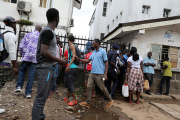 People gather at the entrance of the Connaught Hospital in Freetown