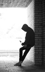 Silhouette of Lonely Teenager Standing with Beer Bottle in Doorway
