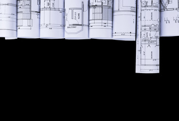 Architectural blueprints and blueprint rolls and a drawing instruments on the black worktable background. Drawing compass plans.Construction background.