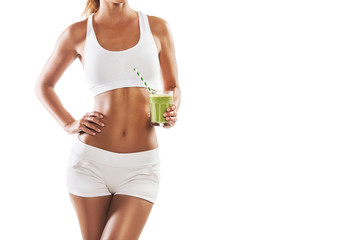 Fit young woman holding a healthy, green smoothie, isolated on white background, body