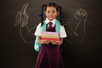Composite image of smiling schoolgirl carrying books