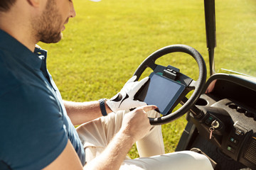 Cropped image of a male golfer sitting in a golf cart