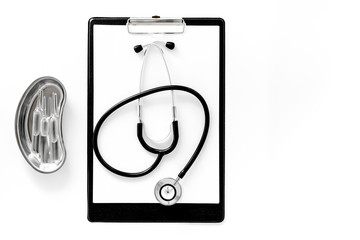 Doctor's table. Clip pad, stethoscope and cuvette with ampoulie on white background top view copyspace