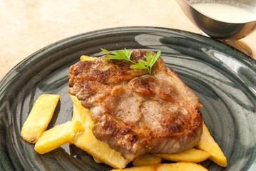 Fototapete - delicious pork steak served with french fries and garlic sauce gourmet style