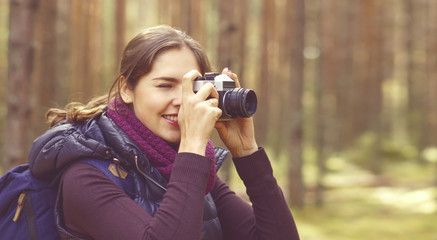 Young, beautiful and happy woman walking in forest and taking pictures. Camp, adventure, trip, hiking concept.