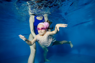 Little girl swims underwater in the pool on a blue background, and mom helps her. Portrait. Close-up. The view from under the water. Landscape orientation