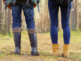 Close-up image of legs of a couple walking in forest. Camp, tourism, hiking concept.